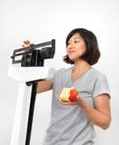 Mujer que se pesa en escala con Apple Imagen de archivo libre de regalías