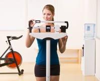 Mujer que se pesa en escalas en club de salud Imagenes de archivo