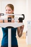 Mujer que se pesa en escalas en club de salud Imágenes de archivo libres de regalías