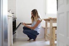 Mujer que se pone en cuclillas abajo en cocina para mirar en el horno Imagenes de archivo
