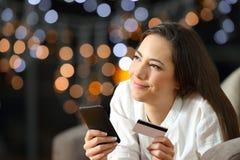 Mujer que se pregunta qué comprar en línea en casa Fotos de archivo