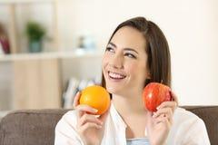 Mujer que se pregunta sobre manzana y naranja Imagenes de archivo