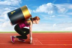 Mujer que se prepara para correr con una batería en ella detrás Imagenes de archivo