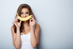 Mujer que se ríe con un plátano Imagenes de archivo