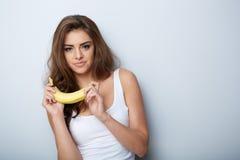 Mujer que se ríe con un plátano Imágenes de archivo libres de regalías