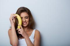 Mujer que se ríe con un plátano Imagen de archivo libre de regalías