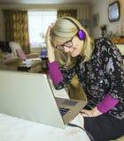 Mujer que se ríe de su pantalla del ordenador portátil, auriculares que llevan imagen de archivo