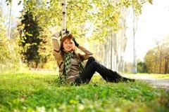 Mujer que se reclina bajo un árbol de abedul en parque del otoño Foto de archivo