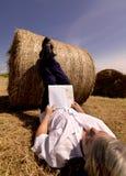 Mujer que se reclina contra la bala de heno del verano Imágenes de archivo libres de regalías