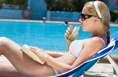 Mujer que se reclina en la piscina Fotos de archivo