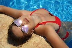 Mujer que se reclina en piscina fotografía de archivo libre de regalías