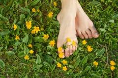 Mujer que se reclina los pies en la hierba Fotografía de archivo