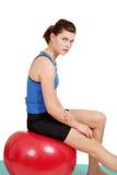 Mujer que se reclina sobre bola roja del ejercicio Fotografía de archivo libre de regalías