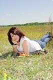 Mujer que se reclina sobre la hierba Imagen de archivo