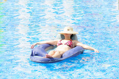 Mujer que se reclina y que broncea en la piscina Imagenes de archivo