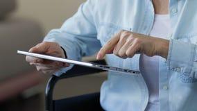 Mujer que se registra en el app móvil en la tableta, cola en línea al centro de rehabilitación almacen de metraje de vídeo