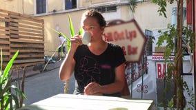 Mujer que se relaja afuera en la taza de la tenencia de la calle de Estambul, el café de consumición o el té en la sol de la maña almacen de video