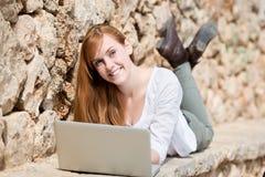 Mujer que se relaja al aire libre con su ordenador portátil Imagenes de archivo