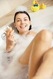 Mujer que se relaja con el vidrio de vino en baño Imagenes de archivo