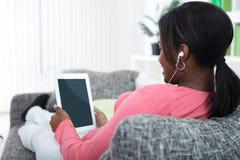 Mujer que se relaja con la tableta Imágenes de archivo libres de regalías