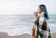Mujer que se relaja con la taza de bebida en costa de mar fotografía de archivo