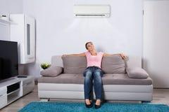 Mujer que se relaja debajo del acondicionador de aire fotografía de archivo