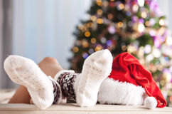 Mujer que se relaja delante del árbol de navidad Imágenes de archivo libres de regalías