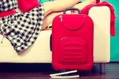 Mujer que se relaja después de embalar la maleta para las vacaciones Foto de archivo