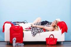 Mujer que se relaja después de embalar la maleta para las vacaciones Imagen de archivo libre de regalías