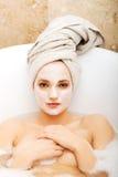 Mujer que se relaja en bañera con la mascarilla Foto de archivo libre de regalías