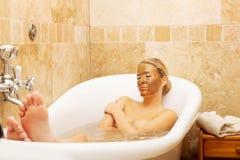 Mujer que se relaja en baño con la máscara del chocolate en cara Foto de archivo libre de regalías