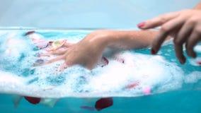 Mujer que se relaja en baño con los pétalos color de rosa y la espuma apacible de la burbuja, tiro macro almacen de metraje de vídeo