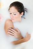 Mujer que se relaja en baño de la leche con las flores Fotos de archivo libres de regalías