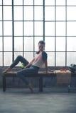 Mujer que se relaja en banco en el gimnasio del desván que mira abajo el piso Imagen de archivo