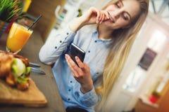 Mujer que se relaja en café en una tabla con el teléfono a disposición, los controles las redes sociales en el zumo de naranja de Imagenes de archivo