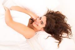 Mujer que se relaja en cama Imagen de archivo libre de regalías