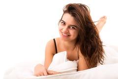 Mujer que se relaja en cama Imagenes de archivo