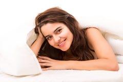 Mujer que se relaja en cama Foto de archivo