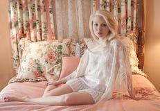 Mujer que se relaja en cama de lujo Foto de archivo libre de regalías
