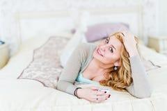 mujer que se relaja en cama usando el teléfono elegante Fotos de archivo libres de regalías