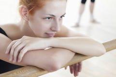 Mujer que se relaja en el ballet Barre In Rehearsal Room Fotos de archivo