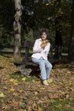 Mujer que se relaja en el banco Imagenes de archivo