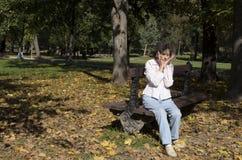 Mujer que se relaja en el banco en otoño Imagenes de archivo