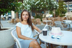 Mujer que se relaja en el café al aire libre - café de consumición y lectura Fotografía de archivo