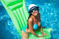 Mujer que se relaja en el colchón en el agua de la piscina en día soleado caliente S imagen de archivo