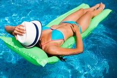 Mujer que se relaja en el colchón en el agua de la piscina en día soleado caliente S imagen de archivo libre de regalías