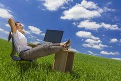 Mujer que se relaja en el escritorio de oficina en campo verde Imagenes de archivo