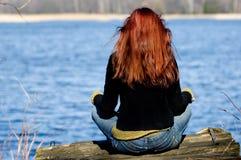Mujer que se relaja en el lago Imagen de archivo