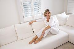 Mujer que se relaja en el país en el sofá blanco Foto de archivo libre de regalías
