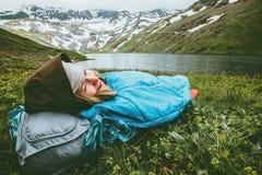 Mujer que se relaja en el saco de dormir que pone en la hierba que goza del lago y de las montañas foto de archivo libre de regalías